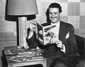 Bud Collyer is smiling while reading the comic book.
