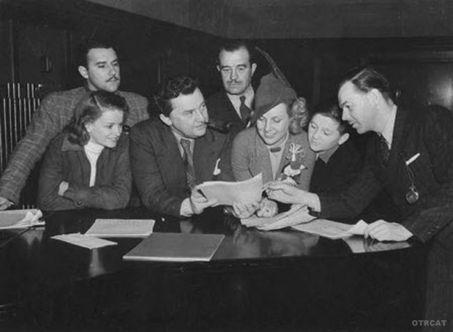Cast of Dr. Christian which debuted in 1937. Standing from left to right: Gale Gordon and Carl Stanton. Leaning on piano, from left to right: Rosemary De Camp as Nurse Judy Price; Jean Hersholt as Dr. Paul Christian; Mary Smith; Walter Tetley; Bill Lawrence, producer.