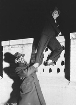 The Green Hornet pulls a man from the wall!