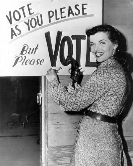 Woman Hammering Nail on Voting Sign with a Gun,