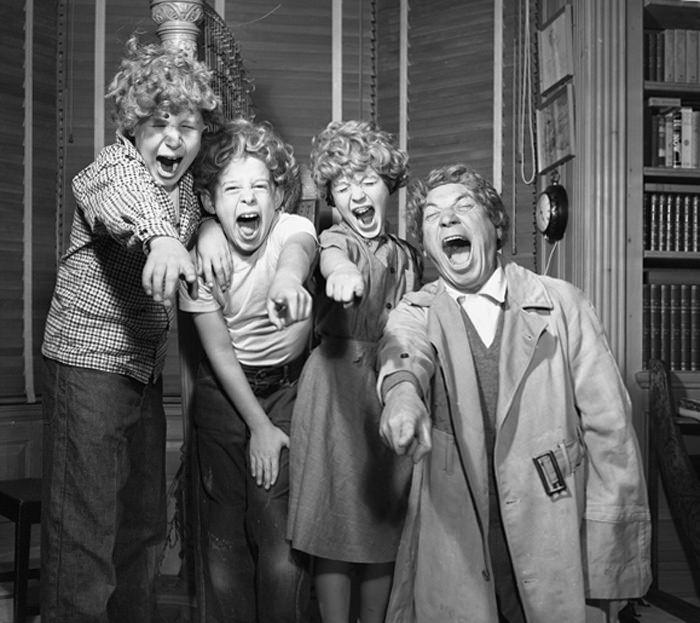 Harpo Marx and three of his children joking around wearing Harpo wigs in Los Angeles, Calif., 1954
