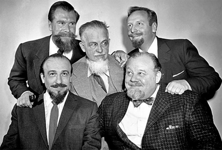 Mitch Miller with four other bearded men: Burl Ives, seated, Cmdr. Edward Whitehead, top left, mystery author Rex Stout, center, and musician Skitch Henderson